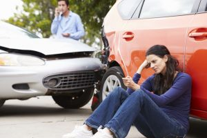 Woman waiting for mobile car repair to fix crashed car